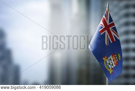 A Small Flag Of Cayman Islands On The Background Of A Blurred Background