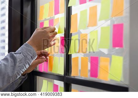 A computer scientist tracks his tasks on the Kanban board. Use of the task control of the agile development methodology. Man attaching a sticky note to the scrum task board in the office