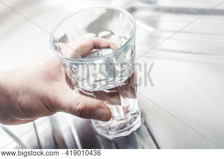 Hand Holding A Drinking Glass Filled Up With Water On A Kitchen Sink