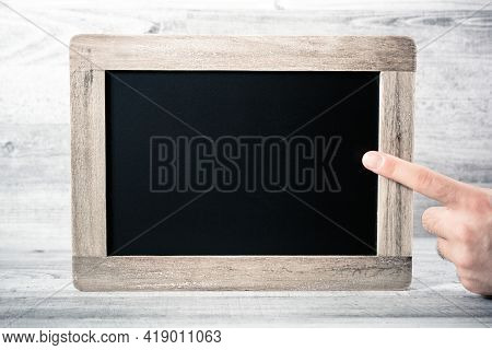 Finger Pointing To A Blank Blackboard With Copy Space In Front Of A Background