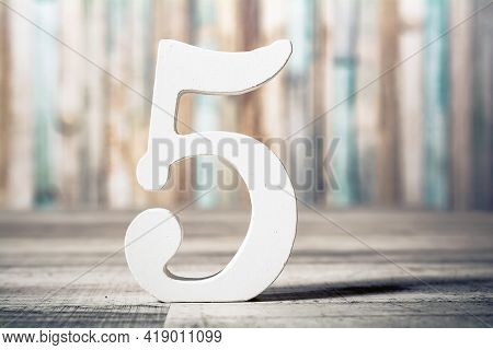 Number 5 Standing On A Gray Wooden Board