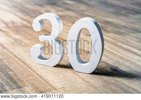 Number 30 Standing On A Brown Wooden Table