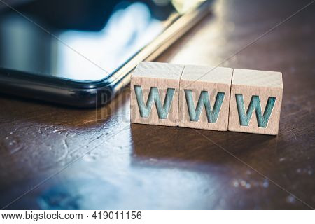 Www Written On Wooden Blocks Next To A Smartphone On A Table