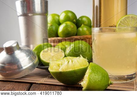 Brazilian Drink Caipirinha, Glass Of Caipirinha, Bottle Of Cachaça, Cocktail Shaker And Lemons On Wo