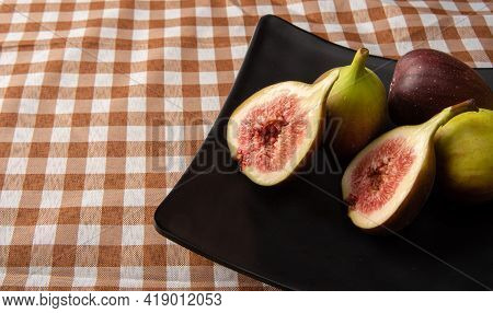 Purple Figs, Purple Figs Open On A Black Plate Over Checkered Tablecloth, Black Background, Selectiv