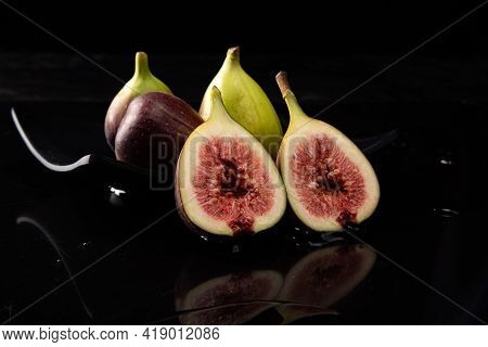 Purple Figs, Purple Figs Open On A Black Plate On Dark Reflective Surface, Black Background, Selecti