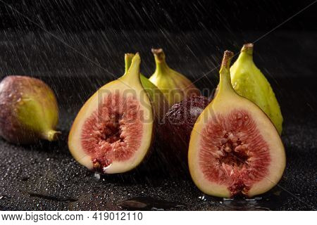 Purple Figs, Open Purple Figs Being Sprayed With Water, Black Background, Selective Focus.