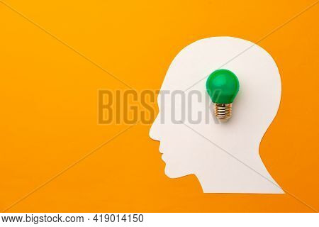 Papercut Head And Light Bulb On Paper Background