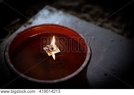 Candle Lights With Flame Glowing On Oil In A Church. Symbol Of Faith And Spirit