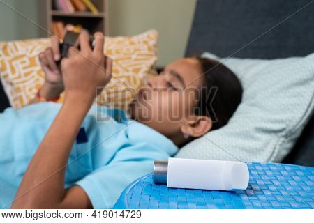 Focus On Inhaler, Sick Asthmatic Girl Kid Playing Game On Mobile Phone Near Inhaler Medication While