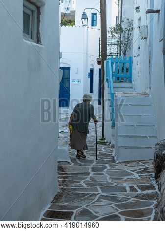 Lefkes, Paros Island, Greece - 27 September 2020: Old Woman With A Can Walking Down A Narrow Street