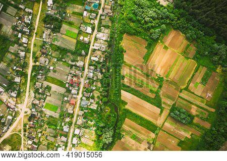 Aerial View Of Vegetable Gardens In Small Town Or Village. Skyline In Summer Evening. Village Garden