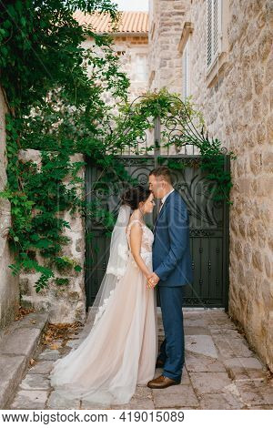 The Bride And Groom Stand Holding Hands In A Small Courtyard Near The Forged Gate, The Groom Kisses