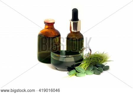 Green Chlorophyll In Cup, Pills And Concentrated Solution In Bottles.  Healthy Detox Drink  And Tabl
