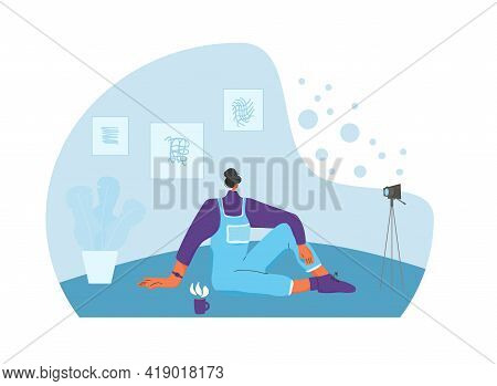 Young Woman Sitting On The Floor With Camera And Laptop. Female Blogger Dressed In Casual Clothes Re