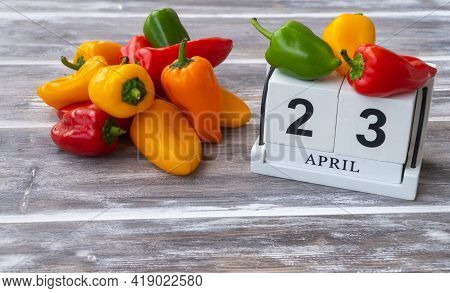 Calendar And Colorful Peppers On A Wooden Background. Selective Focus. April 23, Pepper Day In Bermu
