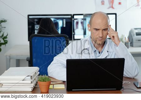 Serious Concentrated General Practitioner Wearing Earphones When Watching Webinar On Laptop, His Col