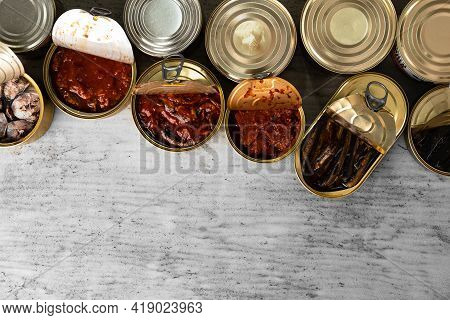 Top View Of Opened Cans With Fish Conserves On Wooden Background