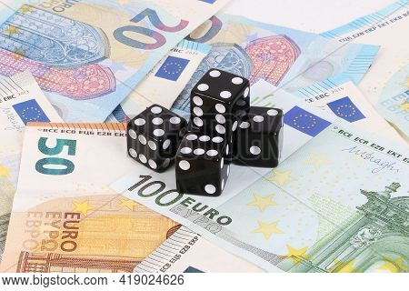Black Dices Are Lying On A Heap Of Different Euro Notes
