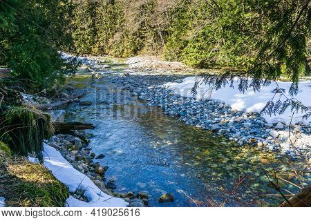 Snow Lines The Shore Of Denny Creek In Washington State.