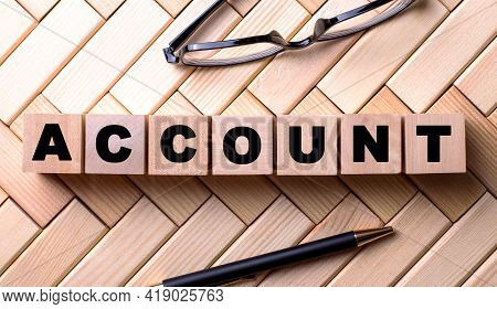 The Word Account Is Written On Wooden Cubes On A Wooden Background Next To A Pen And Glasses.