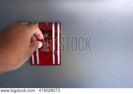 The Hand Is Pulling The Fire Alarm On The Wall. Fire Alarm Switch In The Building.fire Alarm Equipme