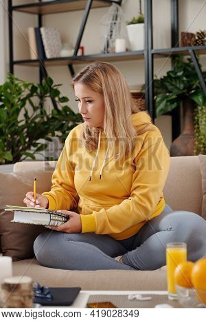 Concentrated Young Woman Studying At Home, Working On Project Or Preparing For Exam