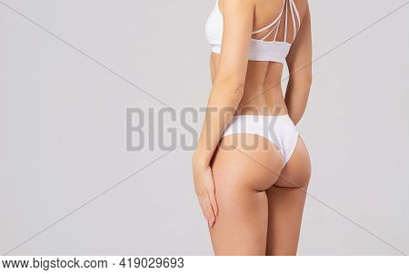 Close-up Of A Beautiful And Fit Female Figure. Studio Photo Of Young Womans Body In Swimsuit.