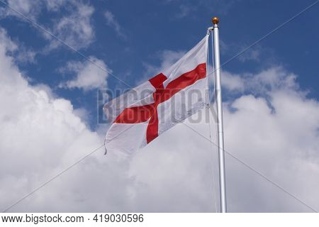 Red And White Flag Of St George England Against Blue Cloudy Sky
