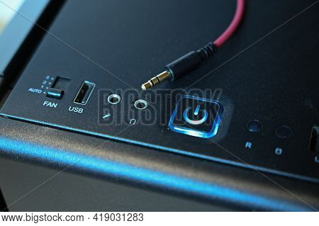 A Red Cable With A Mini Jack Connector Lies On The Computers System Unit Near The Headphone Jack