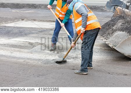 Two Road Workers In Bright Orange Reflective Vests Prepare The Old Pavement For Renovation And Remov