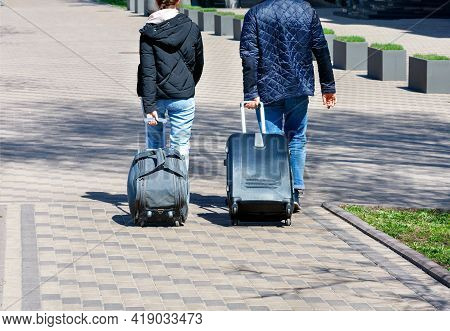 A Young Couple, A Man And A Woman, Walk Along The Cobbled Sidewalk, Traveling On A Sunny Day, Carryi