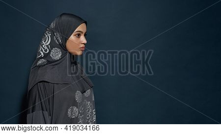Profile Of Young Arabian Girl In Hijab Looking To Side While Posing On Dark Blue Background With Cop