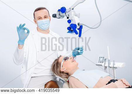 A Male Dentist In Mask And A Patient Woman In The Dentist Chair. Male Dentist Examining Patient Look