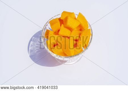 Close Up Of Cantaloupe Fresh Melon Cubes In Glass Bowl On Beige Background. Organic Vegetarian Healt