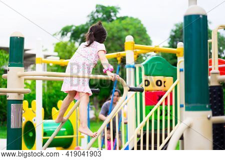 Rear Back View Of Cute Asian Girl Climbing The Playground Equipment. Happy Healthy Kid Likes To Exer