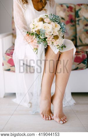 Barefoot Bride In A Lace Robe Sits On A Sofa In A Hotel Room And Holds A Wedding Bouquet In Her Hand