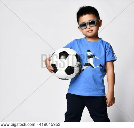 Studio Portrait Of Preschool Little Asian Boy In Trendy Trendy Sunglasses Blue T-shirt Print Soccer