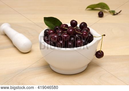 Yummy Berries Cherries In A Bowl And A Pestle On The Wooden Table