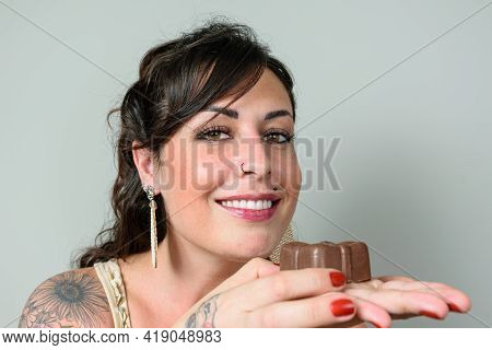 Closeup Of Brazilian Woman Smiling And Looking At The Camera, Holding A Traditional Brazilian Sweet,
