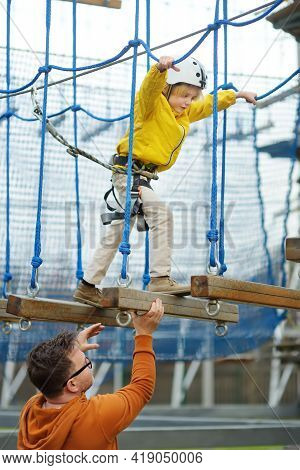 Little Boy Having Fun In Adventure Park For Children Among Ropes, Stairs, Bridges. Father Helping So