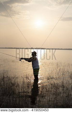 Fishing Man At Sunset. Silhouette And Reflection.