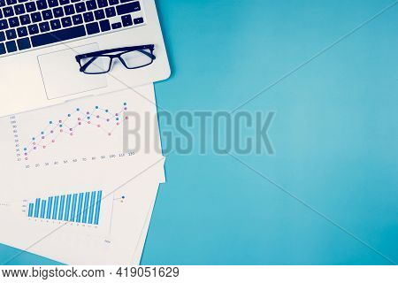 Laptop Computer And Documents Report Statistic Financial With Graph And Chart And Glasses On Desk, F