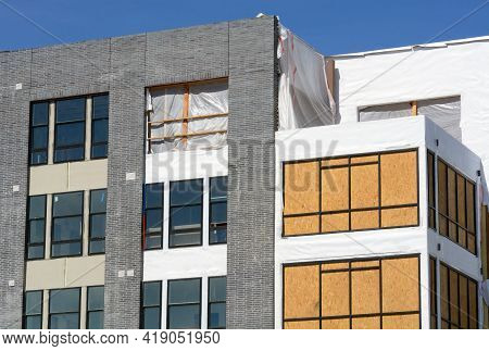 Construction Of New Building With Windows , Plywood And Wrap Still On Exterior Before Installation O