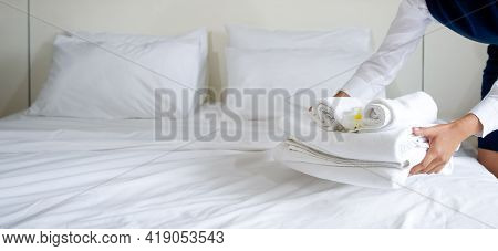 Hotel Maid Putting Set Of Towel With White Flower On The Bed. Staff In Blue Uniform Preparing Room F