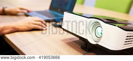 Close Up Computer Projector On Meeting Tables With Technician Setup Laptop At Boardroom Or Seminar O