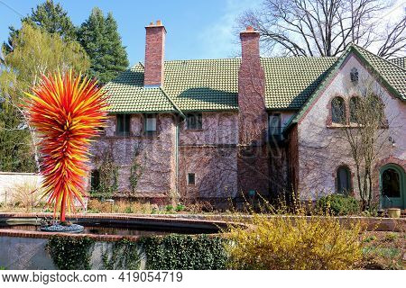 April 26, 2021 In Denver, Co:  Contemporary Glass Art Sculpture On A Courtyard In Front Of A Tudor S
