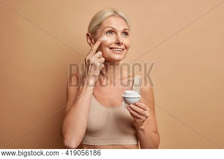 Smiling Middle Aged Blonde Woman Uses Beauty Product Applies Nourishing Face Cream To Moisturise Ski