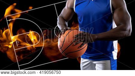 Composition of midsection of basketball player holding basketball over basketball court and fire. sport and competition concept digitally generated image.