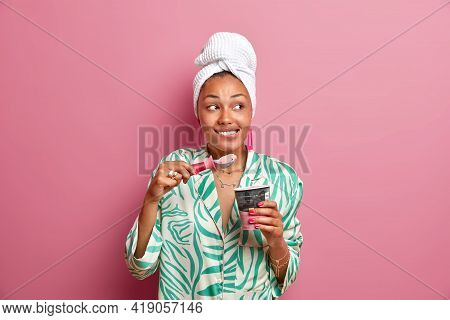 Indoor Shot Of Cheerful Dark Skinned Young Woman Bites Lips Enjoys Eating Appetizing Cold Ice Cream